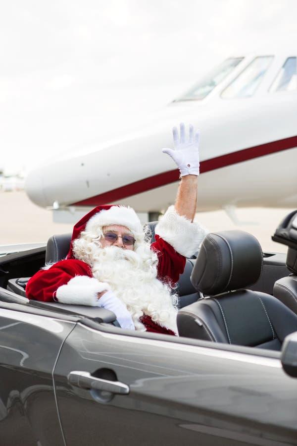 在敞篷车的圣诞老人挥动的手反对私有 库存图片
