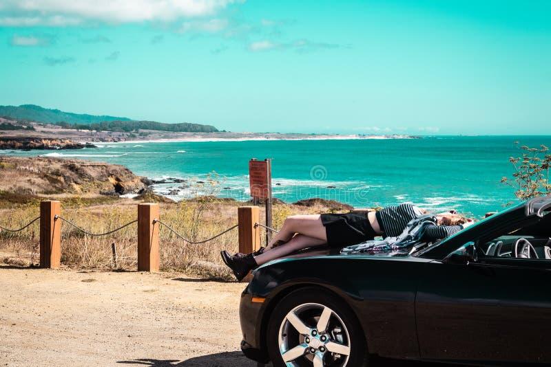 在敞篷车顶部的女孩在半月湾,加利福尼亚 免版税库存图片