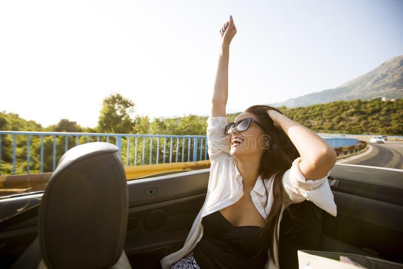 在敞蓬车的年轻有吸引力的妇女驱动在海边 免版税库存照片