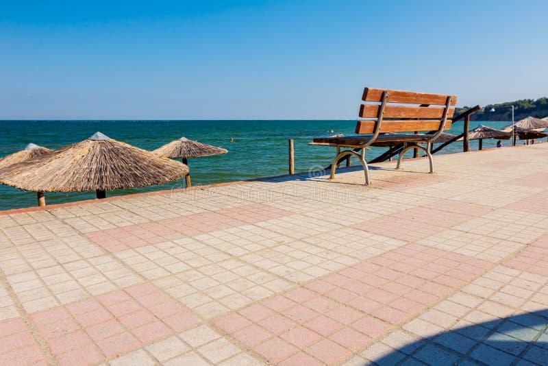 在散步的空的长木凳在c旁边的公开海滩上 免版税库存照片