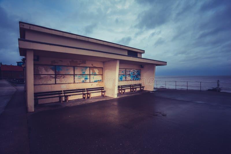 在散步的老大厦在海旁边 免版税库存照片