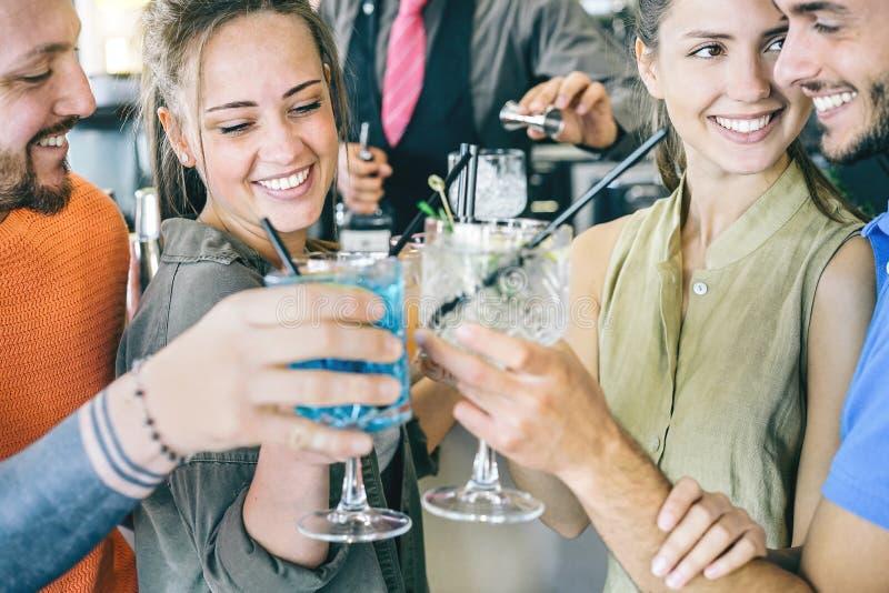 在敬酒在酒吧的爱的两对年轻夫妇鸡尾酒-约会一起做的愉快的朋友与口味饮料的欢呼 库存照片