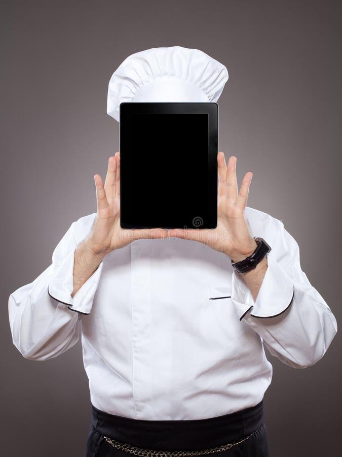 在数字式片剂之后的主厨 免版税库存图片