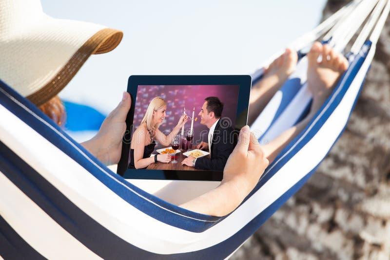 在数字式片剂的妇女观看的电影在吊床 免版税库存图片