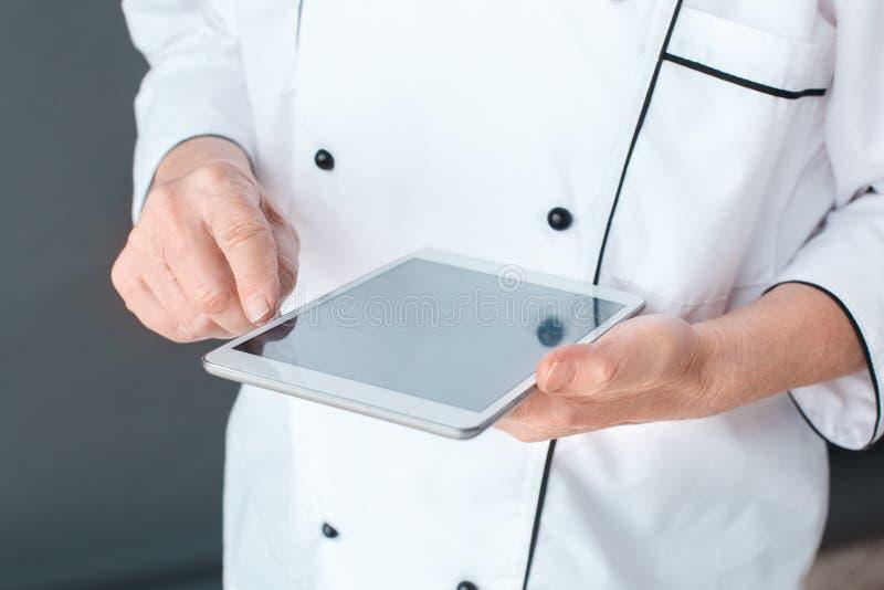 在数字片剂特写镜头的灰色tocuhing的屏幕上隔绝的资深厨师演播室身分 图库摄影
