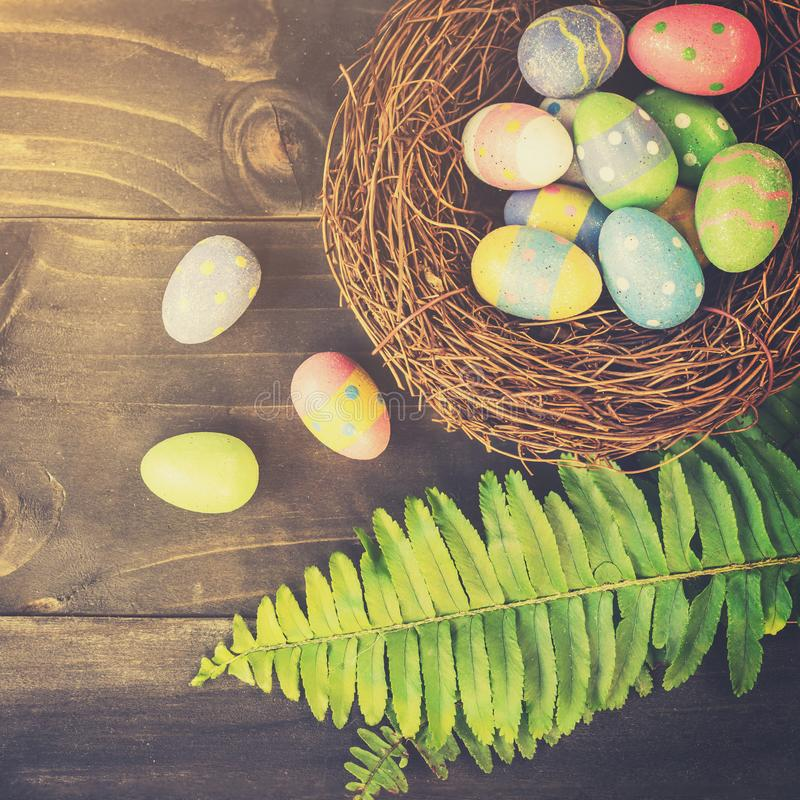 在整洁和绿色事假的五颜六色的复活节彩蛋在与空间的桌木背景 免版税库存图片