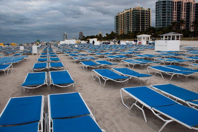 在整洁的行的蓝色sunbeds在南海滩,迈阿密;风暴日,灰色云彩 库存图片