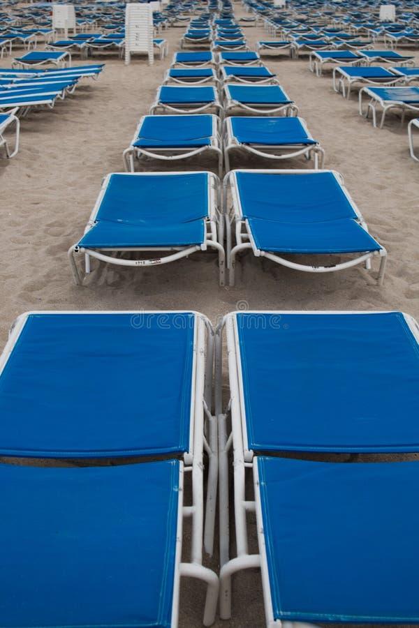 在整洁的行的蓝色sunbeds在南海滩,迈阿密;风暴日,灰色云彩 免版税库存照片