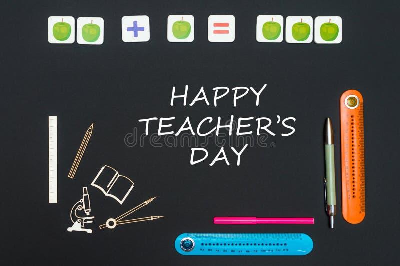在文具供应和文本愉快的老师` s天上在黑背景 免版税图库摄影