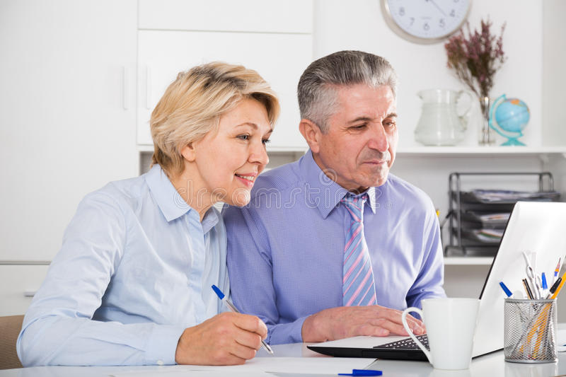 在文件的成熟雇员工作 免版税库存图片