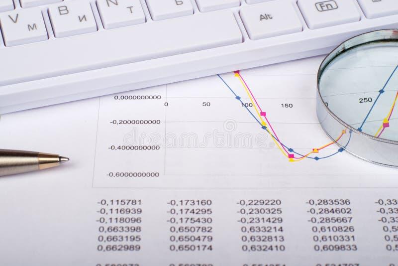 在文件的有柄小镜与键盘 免版税库存图片