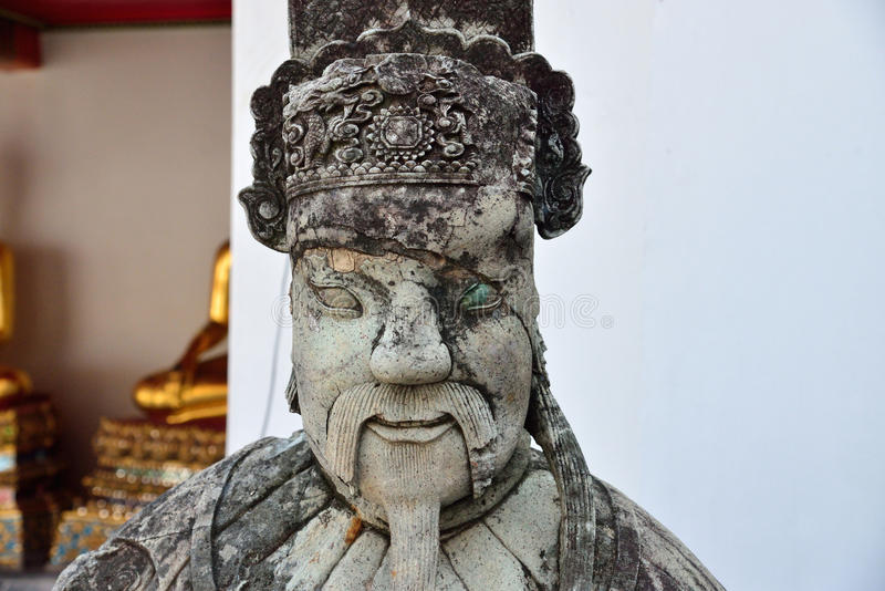 在斜倚的菩萨的Wat Pho寺庙,曼谷,泰国的中国监护人石头雕象 图库摄影