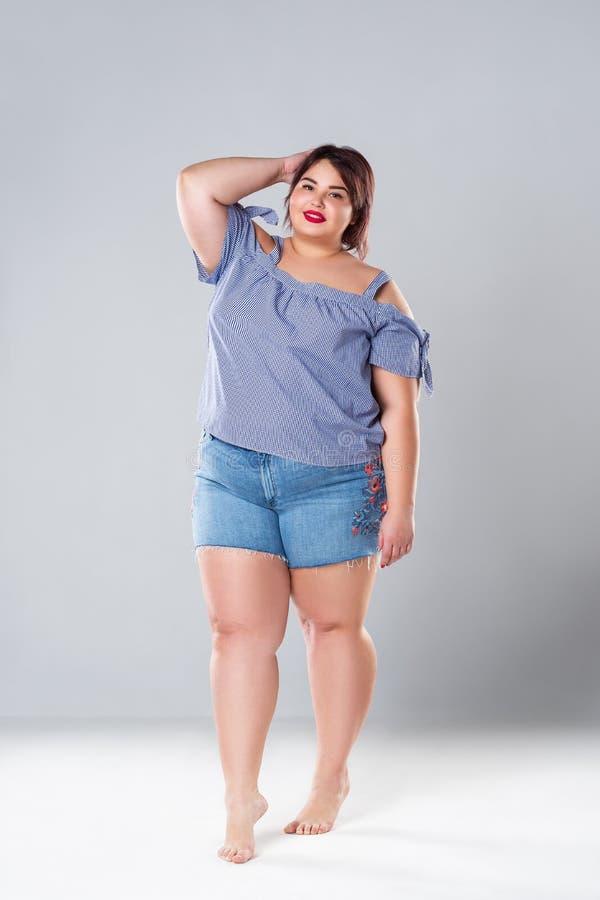 在斜纹布短裤的正大小时装模特儿,灰色背景的肥胖妇女 库存照片