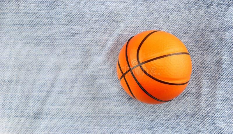 在斜纹布背景的小玩具篮球 免版税库存图片