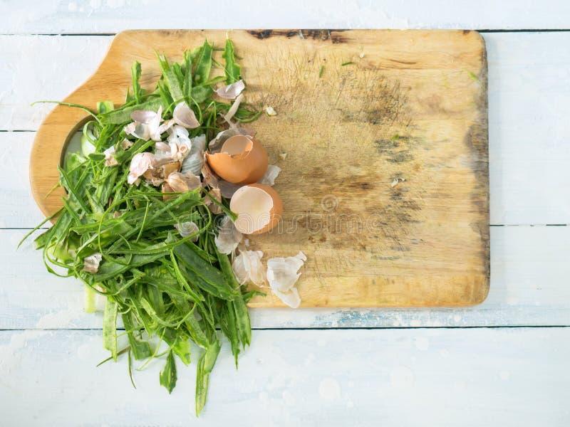 在斩肉板的被剥皮的里奇金瓜壳、大蒜和蛋壳 免版税库存图片