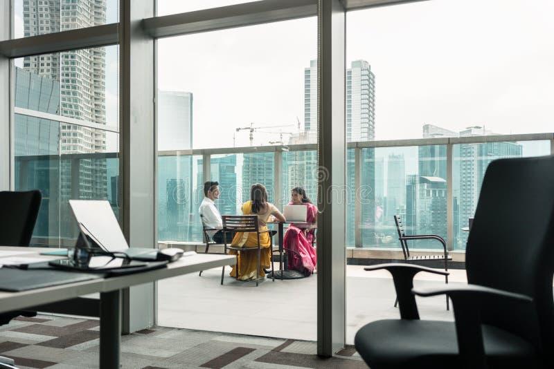 在断裂期间的印地安雇员在一个现代大厦的大阳台 库存照片