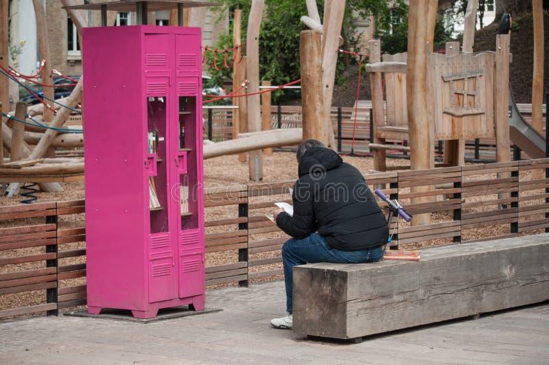 在斯坦贝奇公园供以人员读从自由书橱的一本书 免版税库存图片