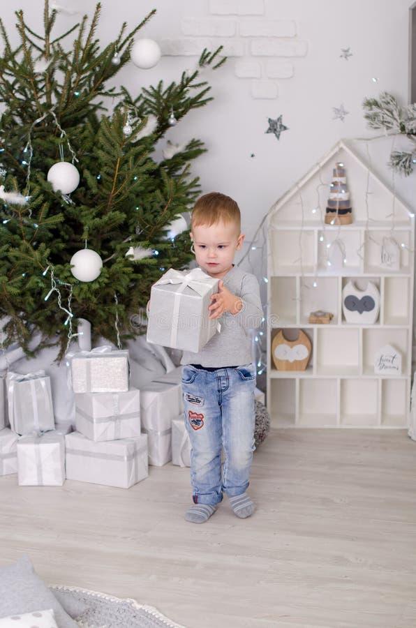 在斯堪的纳维亚样式的新年,圣诞树,有孩子的妈妈,儿童` s玩具,睡眠婴孩 库存照片