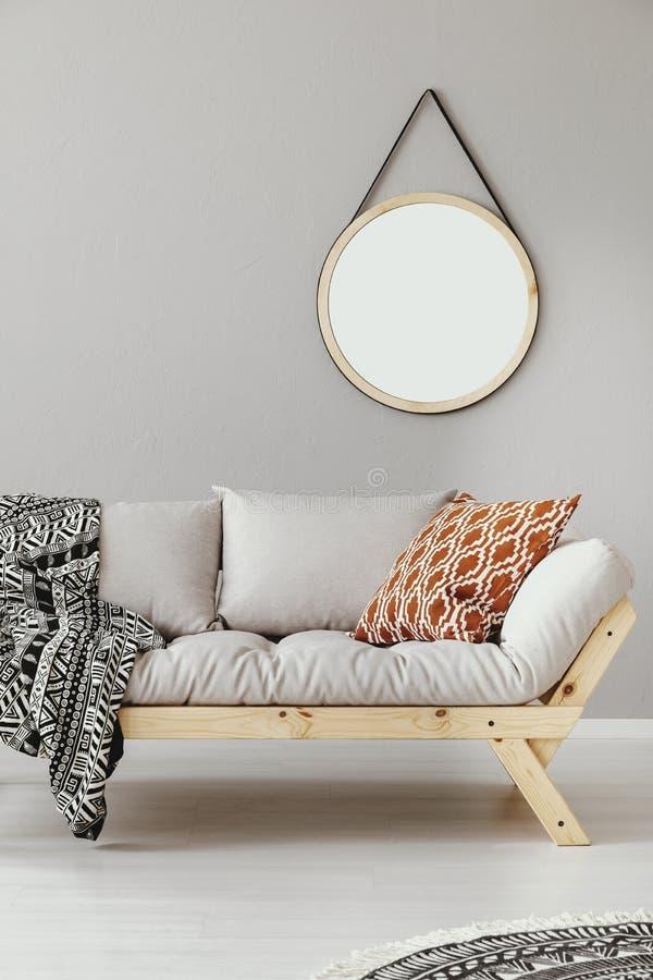在斯堪的纳维亚长椅上的镜子与被仿造的枕头和毯子 免版税库存图片