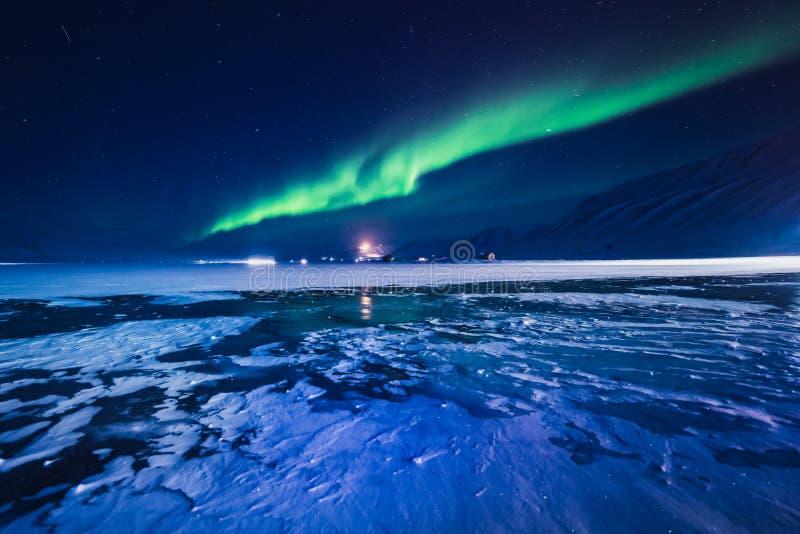 在斯瓦尔巴特群岛,朗伊尔城,卑尔根群岛,挪威墙纸山的北极光  免版税库存图片