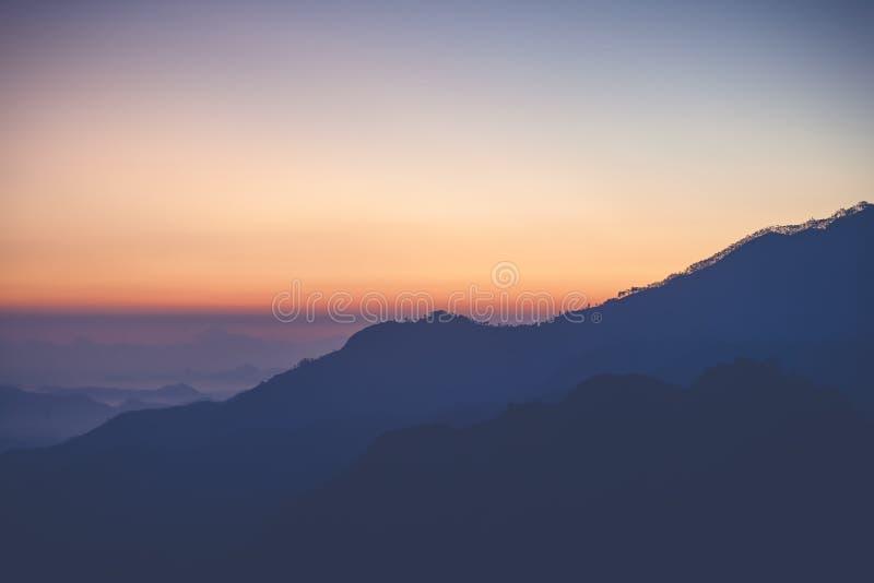 在斯里兰卡的山的明亮的惊人的惊人的日落黎明,太阳上升从山的后面 美丽minimalistic 免版税库存照片