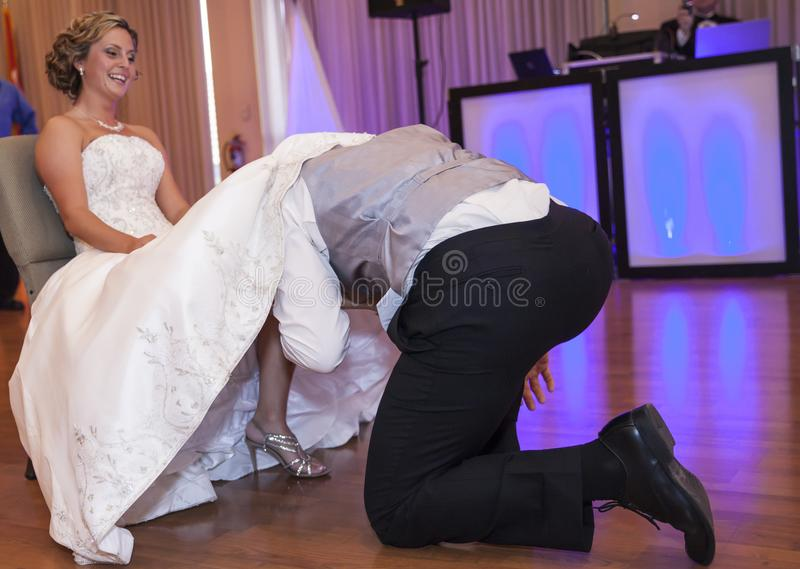 在新娘下的新郎穿戴离开袜带 免版税图库摄影