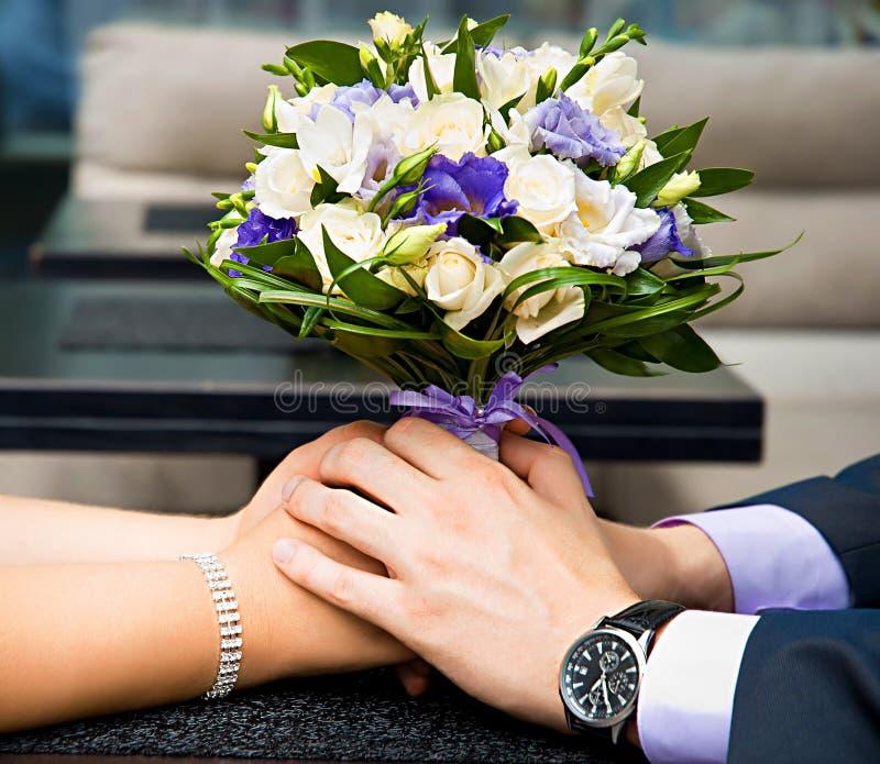 在新娘和新郎手的美丽的婚礼花束 库存照片