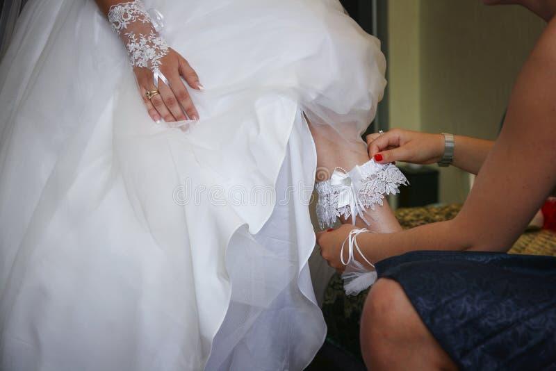 在新娘的腿的佩带的袜带 免版税库存图片