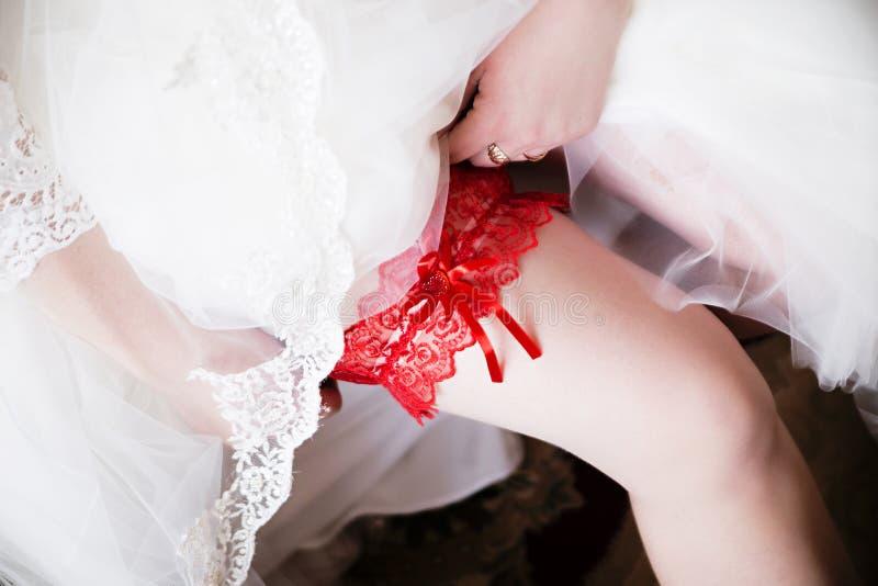 在新娘的腿,早晨新娘的红色袜带,新娘佩带a 免版税库存图片