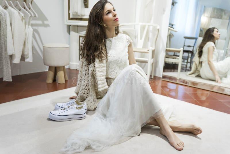 在新娘礼服打扮的美女,当坐地板在镜子附近时 免版税库存图片