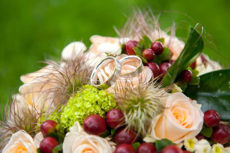 在新娘花花束顶部的银色结婚戒指 免版税图库摄影