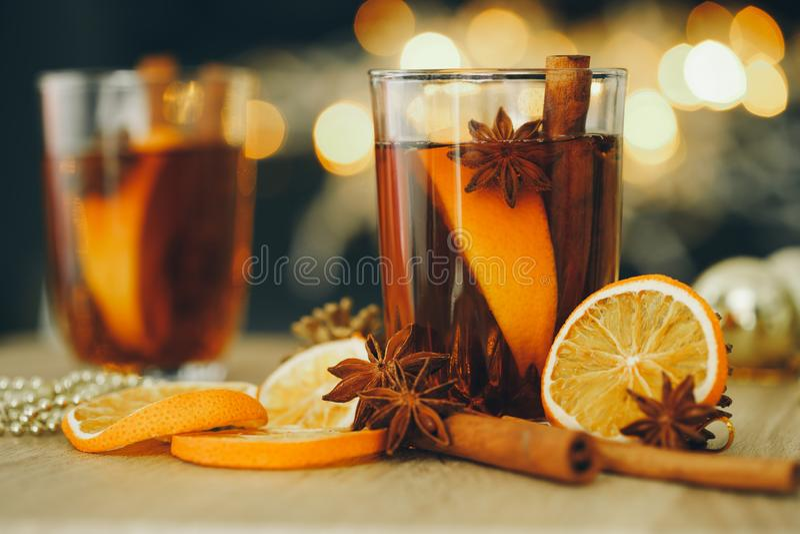在新年聚会和可口圣诞节饮料的夜庆祝的加香料的热葡萄酒 免版税库存照片