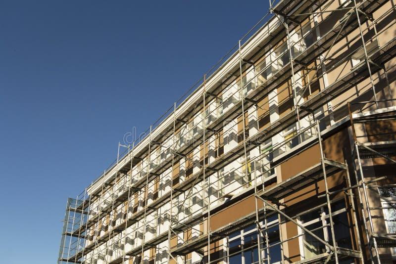 在新房建设中,白色墙壁和窗口附近的脚手架, 免版税库存照片