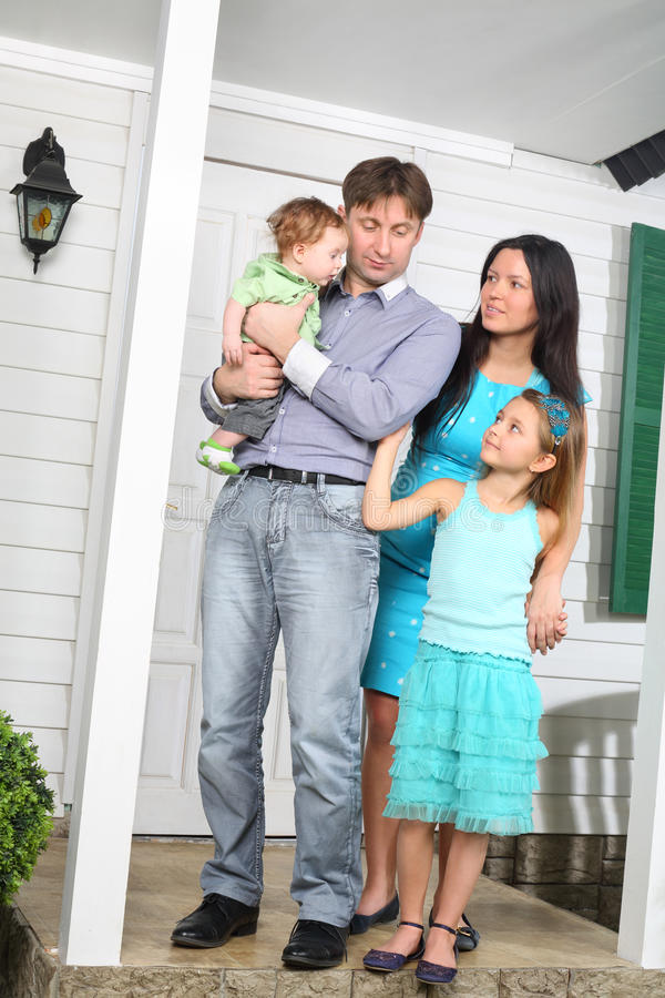 在新房门廊的愉快的年轻家庭立场  库存图片