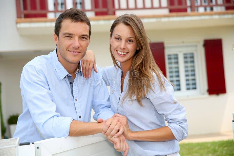 在新的家前面的爱夫妇 免版税库存图片