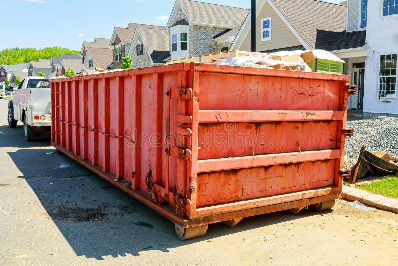 在新的家附近的垃圾容器,红色容器,回收和废建造场所背景的 库存照片