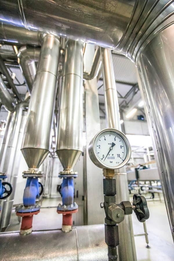 在新的明亮的工厂用管道运输不锈钢建筑 免版税库存照片