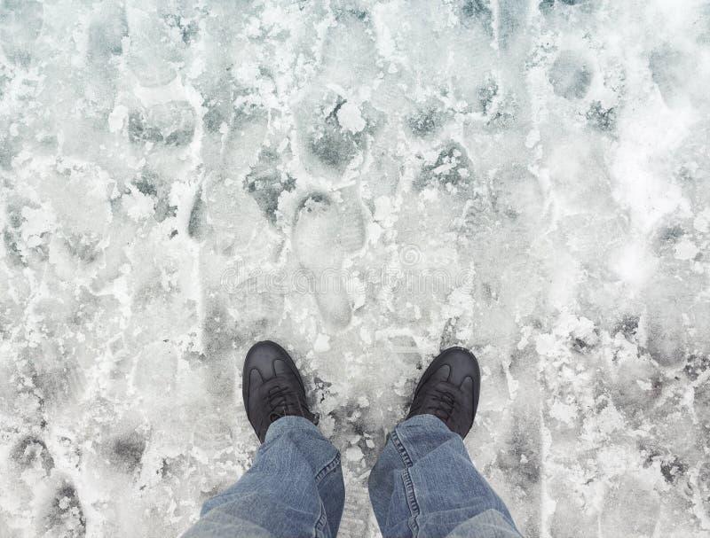 在新的鞋子的男性脚在湿肮脏的雪站立 免版税库存图片