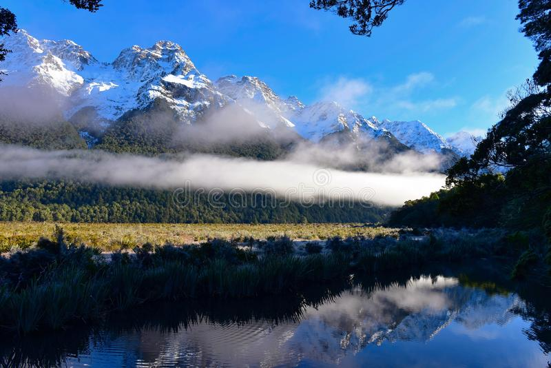 在新西兰反映湖和它雪山的完善的反射 免版税库存图片