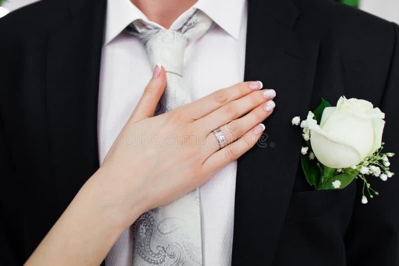 在新郎和bride's手衣服的婚礼钮扣眼上插的花  免版税库存照片