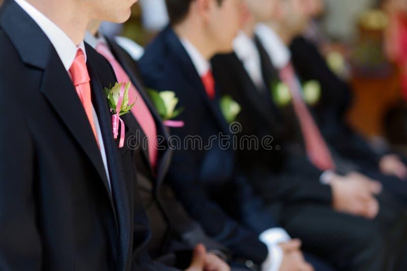 在新郎的人夹克的婚礼钮扣眼上插的花  免版税库存照片