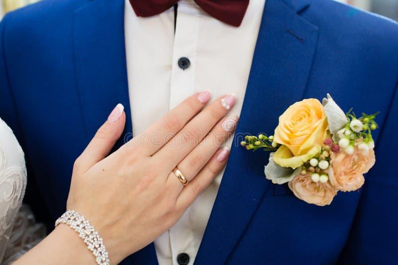 在新郎的衣服的婚礼钮扣眼上插的花 免版税库存图片