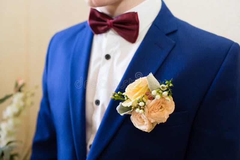 在新郎的衣服的婚礼钮扣眼上插的花 库存图片
