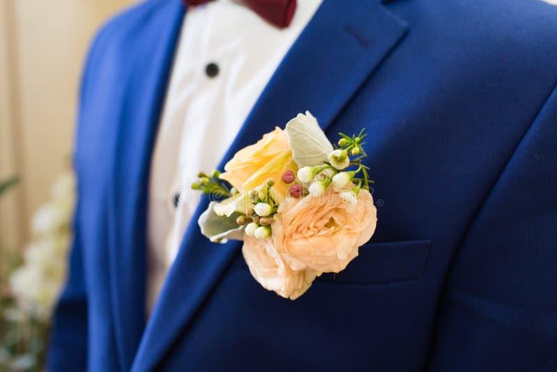 在新郎的衣服的婚礼钮扣眼上插的花 免版税库存照片