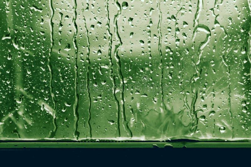 在新鲜玻璃窗的绿色的背景雨珠 免版税库存照片