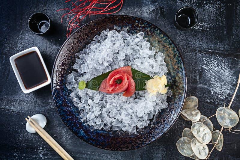 在新鲜的切的金枪鱼生鱼片的顶视图在有冰的碗服务在黑暗的背景 日本料理生鱼片 日本餐馆菜单 库存照片