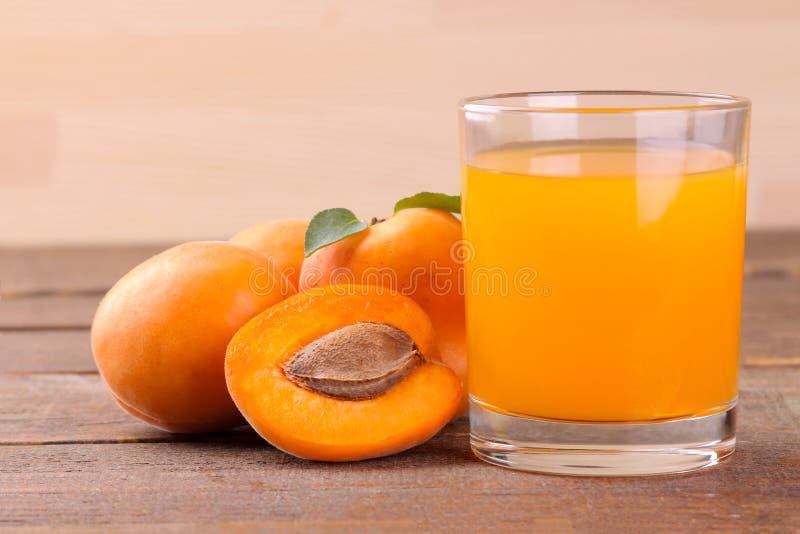 在新鲜的杏子旁边的杏子汁在棕色木背景 免版税库存照片