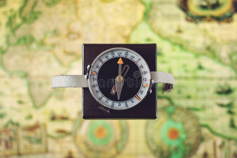 在方形框的罗盘航向北部反对被弄脏的绿色地图背景 哥伦布日,旅行,旅游业概念 库存照片
