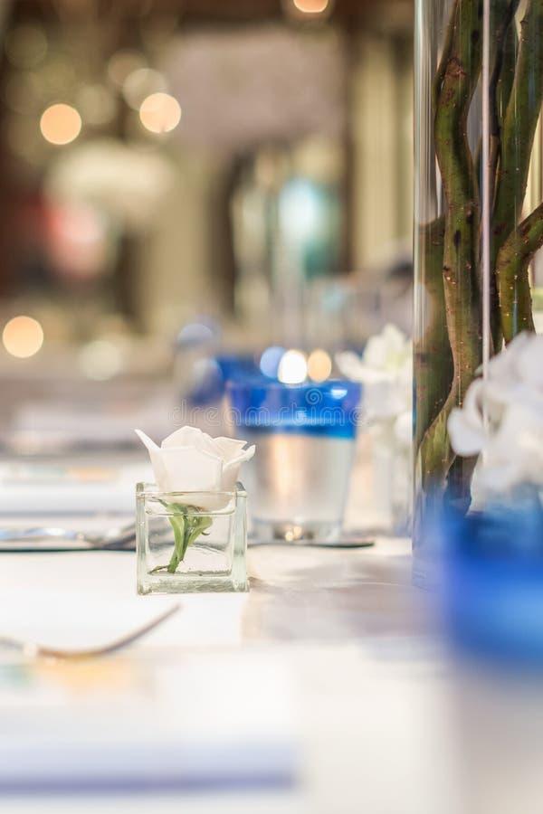 在方形的杯子的白色玫瑰在餐桌设定 图库摄影