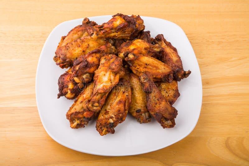 在方形的白色板材的烤鸡翼 免版税库存照片